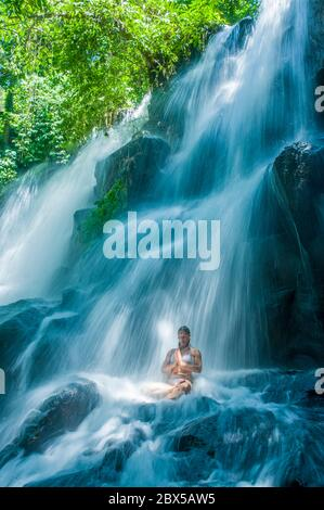 attractive woman sitting at rock in yoga pose for spiritual relaxation serenity and meditation at stunning beautiful waterfall and rain forest in Bali