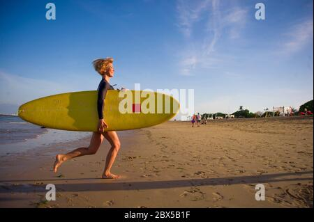 young attractive and happy blonde surfer girl in beautiful beach carrying yellow surf board running out of the sea enjoying summer holidays at tropica