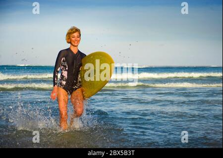 young attractive and happy blonde surfer girl in beautiful beach carrying yellow surf board walking out of the sea enjoying summer holidays at tropica