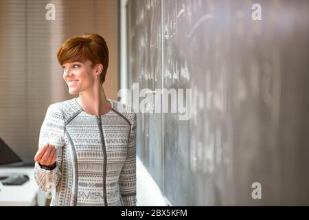 Pretty young elementary school, college teacher writing on chalkboard, blackboard during a lesson, education concept - Stock Photo