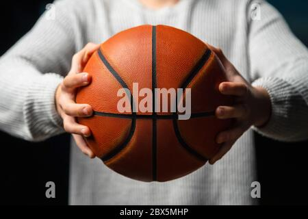 Close up of professional basketball player holding a ball in the hand. Street basketball athlete preparing for competition. Concept of success, scorin