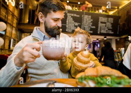 Happy handsome bearded Caucasian man, father, sitting at the table with his little son and holsing cup of latte or cocoa drink. Little cute boy