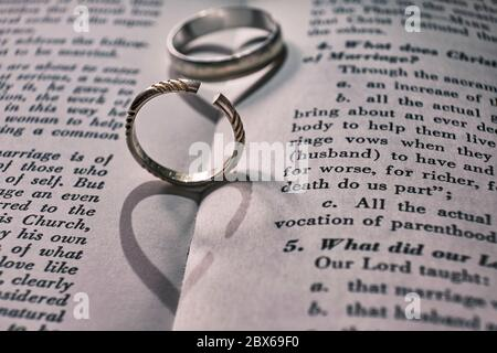 Two wedding bands, one has been cut off on a book with text about marriage. The shadows from the rings make the shape of a heart, and a broken heart. - Stock Photo