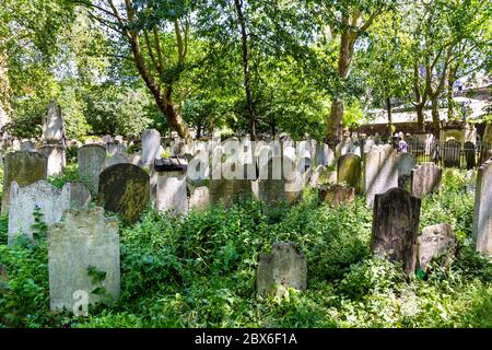 Old overgrown headstones at the Victorian Bunhill Fields Burial Ground, Old Street, London, UK - Stock Photo