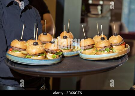 Waiter carrying a tray of appetizers. Outdoor party with finger food, burgers, sliders. man hold tray with burger at restaurant. Men's hands hold a - Stock Photo