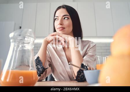 Thoughtful young woman having breakfast at home