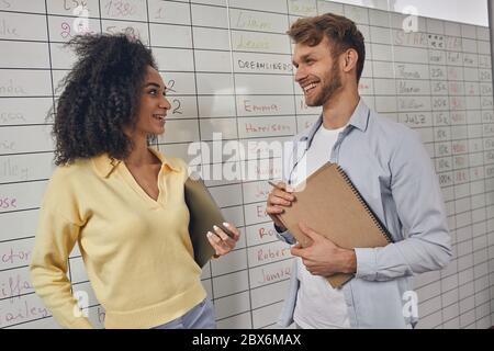 Female employee looking at her merry coworker