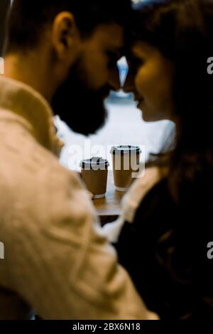 Close up portrait of young romantic couple drinking coffee in paper cups, sitting in a cozy cafe, touching foreheads and enjoying moments together