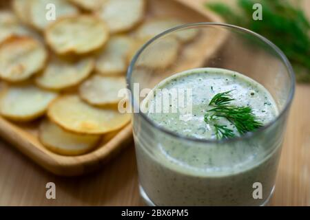 Dill and sour cream dip for homemade potato chips made vegan: healthy snack with dill, tahini, water, vinegar and lemon juice in a glass. Thinly slice - Stock Photo