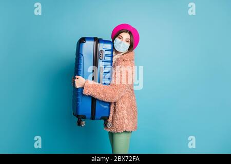 Profile side view portrait of her she fashionable girl holding embracing big bag wearing gauze safety mask open border destination isolated bright - Stock Photo