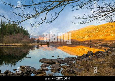 Scenic view of the Snowdon Horseshoe mountains at sunrise, reflected in the still water of Llynnau Mymbyr, Snowdonia National Park, North Wales, UK.