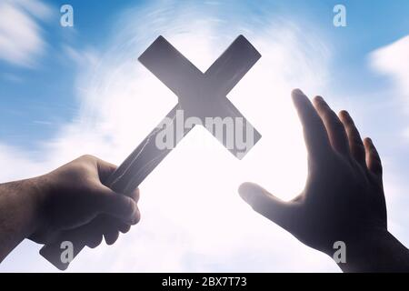 First person view photo of a male hands holding a cross on a bright light shine with blue skies background. - Stock Photo