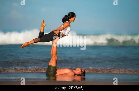outdoors lifestyle portrait young attractive and concentrated couple of yoga acrobats practicing acroyoga balance and meditation exercise on beautiful