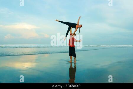 healthy and attractive fit couple of acrobats  doing acroyoga balance and meditation exercise on beautiful desert beach practicing balance and harmony