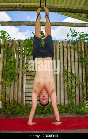 outdoors yoga workout - attractive and happy man doing aero yoga on red mat hanging from ropes training handstand body balance and flexibility in harm - Stock Photo