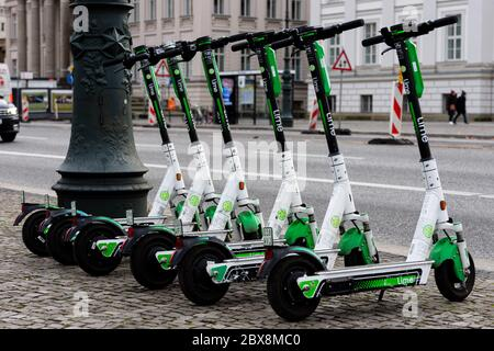 A Row of six standing electric escooter or e-scooter of the company LIME on the sidewalk in Berlin - Stock Photo