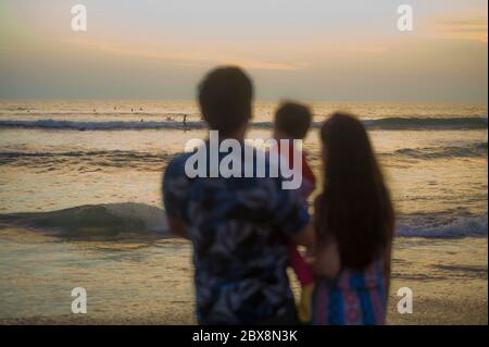 blurred silhouette of young happy and beautiful Asian Chinese couple holding baby girl daughter enjoying sunset beach together looking at the sea in r