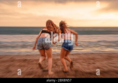back portrait of two happy and attractive young women girlfriends holding hands on the beach running to the sea under beautiful sunset light enjoying - Stock Photo