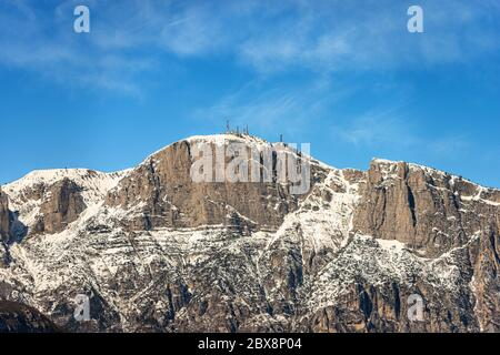 Peak of the Paganella or cima Roda (2125 m), snow caped Alps with the antennas of the weather station, seen from the Trento, Trentino, Italy.