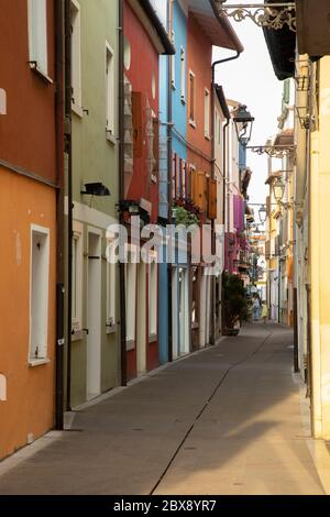 Tourism in Veneto and point of interest among the narrow alleys  and maritme houses to Caorle seaport with bicycles  and colored houses.
