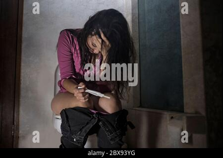 young scared and desperate pregnant woman or teenager girl checking positive result on predictor test sitting on toilet WC crying in unwanted pregnanc - Stock Photo
