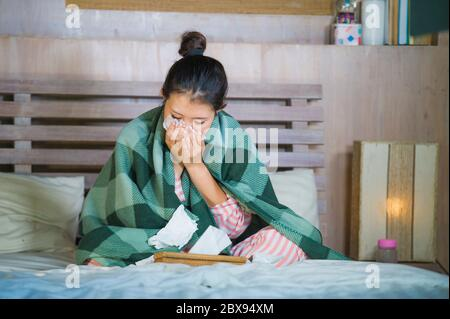 young beautiful and sweet Asian Korean girl in pajamas sick at home bedroom suffering cold and flu taking temperature with thermometer in bed blowing - Stock Photo