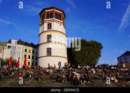 "The historic ""Schlossturm"" (castle tower) in Düsseldorf Old Town with people sitting on the steps and enjoying the sun. - Stock Photo"