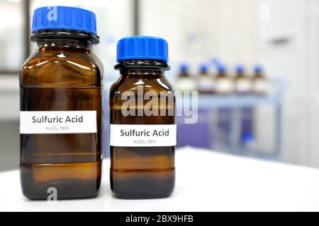 Strong sulfuric acid chemical in brown amber glass bottle inside a laboratory with copy space. - Stock Photo