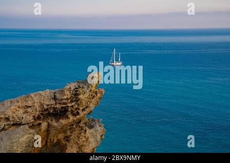 View at the sea from rocks on a sailing boat - Stock Photo