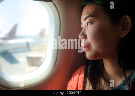 young happy and beautiful Asian Korean tourist woman smiling excited sitting in airplane by the window arriving destination in aircraft transportation