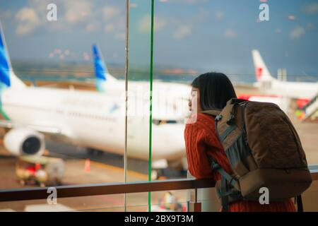 young happy and excited Asian Chinese student woman with backpack at airport departure lounge watching aircraft through glass window smiling ready for