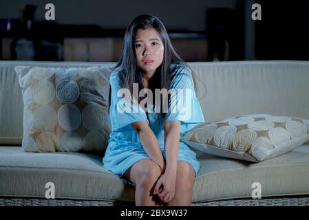 dramatic lifestyle portrait of young beautiful sad and depressed Asian Korean woman at home sofa couch feeling overwhelmed suffering anxiety crisis an - Stock Photo