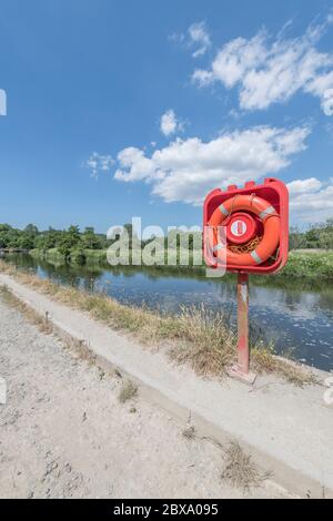 Sunlit bright orange-red lifebuoy ring in quayside housing on River Fowey at Lostwithiel. For safety, danger, staying afloat, possibly risk assessment - Stock Photo