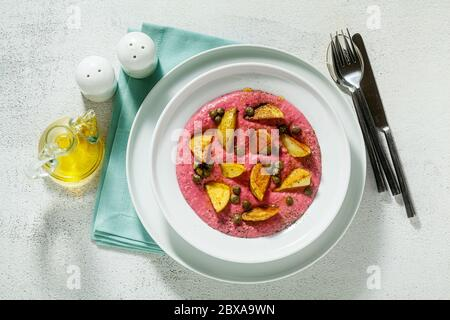 summer dish with pink hummus from cannellini beans and beets with fried potatoes and capers in a plate on the table - Stock Photo