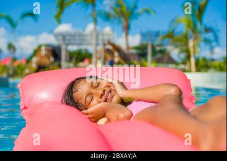 lifestyle outdoors portrait of young happy and cute female child having fun with inflatable airbed in holidays resort swimming pool smiling carefree a - Stock Photo