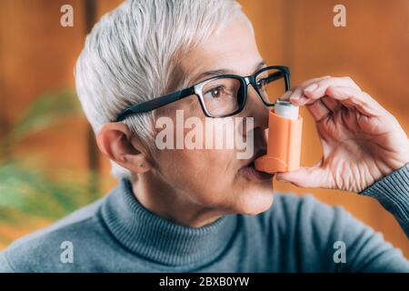 Senior woman inhaling medicine from asthma pump - Stock Photo