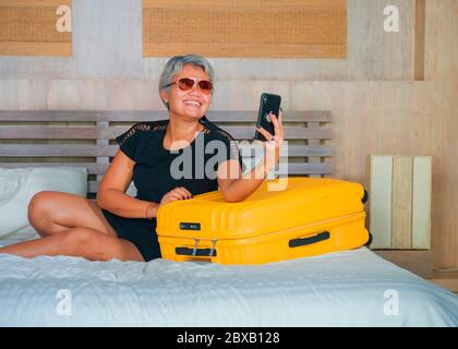 travel and selfie. natural lifestyle portrait of happy and attractive 40s to 50s mature Asian tourist woman with grey hair arriving in hotel room in b - Stock Photo