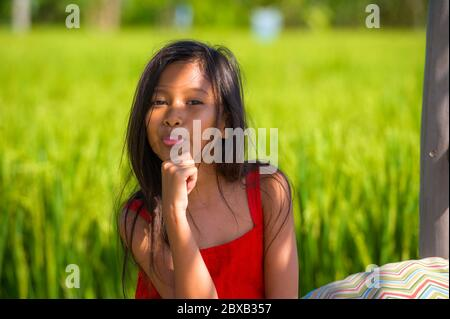 outdoors lifestyle portrait of beautiful and sweet young girl happy posing doing playful faces tongue out, the child dressed in a red dress isolated o