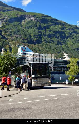 Tourists board a Mercedes-Benz Tourismo coach operated by local company Angels Buss in Geiranger, Norway. Behind is TUI cruise ship Marella Discovery. - Stock Photo