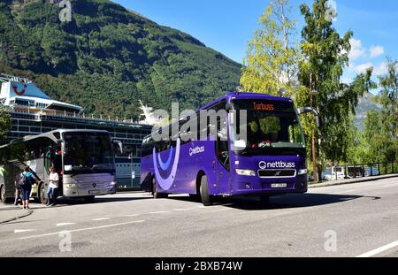 Nettbuss Volvo B12B UF 37926 pulls out of the coach departure point in Geiranger, Norway, while tourists board a Mercedes-Benz Tourismo coach operated - Stock Photo