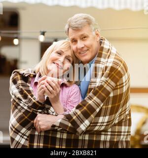 Aged couple embracing each other under warm plaid on camping vacation outdoors - Stock Photo