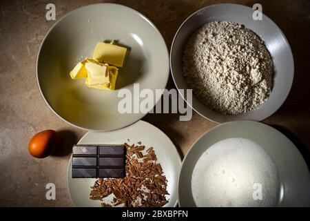 Ingredients for sweet recipe. Egg, butter, flour, chocolate, sugar. Top view. - Stock Photo
