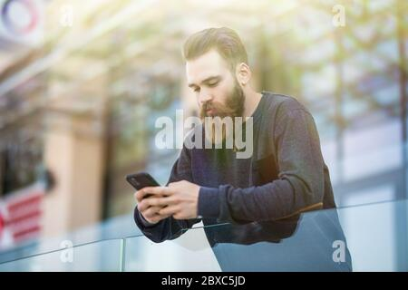 Portrait of bearded young man dressed in casual wear holding smartphone in hand and chatting online in social networks.Hipster guy in denim wear insta - Stock Photo