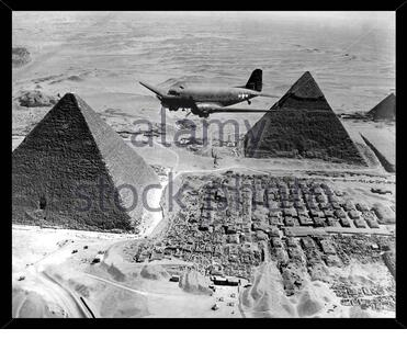 Best WW pictures - American Douglas C-47 Skytrain Air Transport Command plane flies over the pyramids in Gizah, Egypt. 1943 - Stock Photo