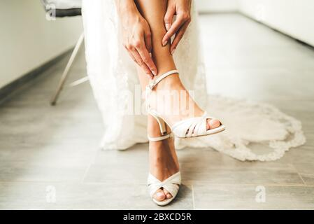 Bride putting on white shoes on her tender feet. Woman in wedding gown sitting on chair - legs close up.