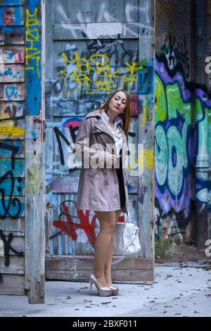 Female young woman 20-25yo 20-25 yo standing in abandoned building full of colorful graffiti artistry on walls whole body legs in sheer tights heels - Stock Photo
