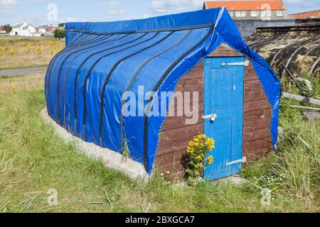 Old fishing boats turned over cut up and used as storage sheds on Lindisfarne, Northumberland, England - Stock Photo