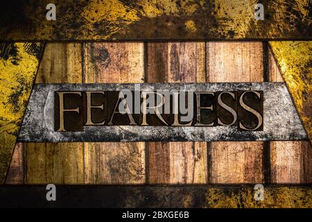 Photo of real authentic typeset letters forming Fearless text on vintage textured silver grunge copper and gold background