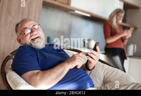 elderly man with a smartphone sitting in a home chair. - Stock Photo