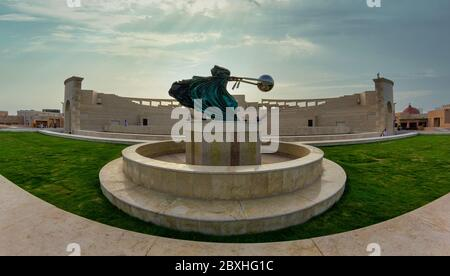The amphitheater in Katara Cultural Village, Doha Qatar panoramic view in daylight  with Force of Nature 2 statue in foreground and clouds in the sky - Stock Photo